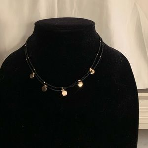Black bead necklace with gold charms